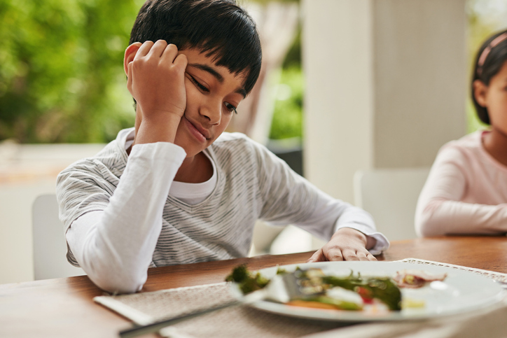 Boy looking unhappily at food on his plate