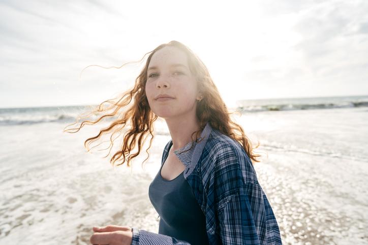teen girl on beach sun-protective behaviors