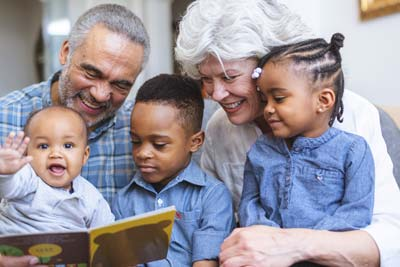 Family reading: Grandparents reading a book to 3 small children who are sitting on their laps.
