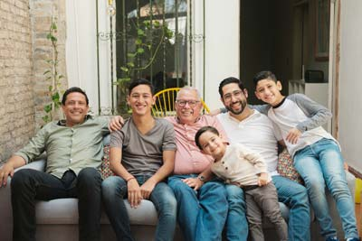 Family sitting together: A group of men and boys, ranging in age from a young child to an older adult, sitting on a couch together.