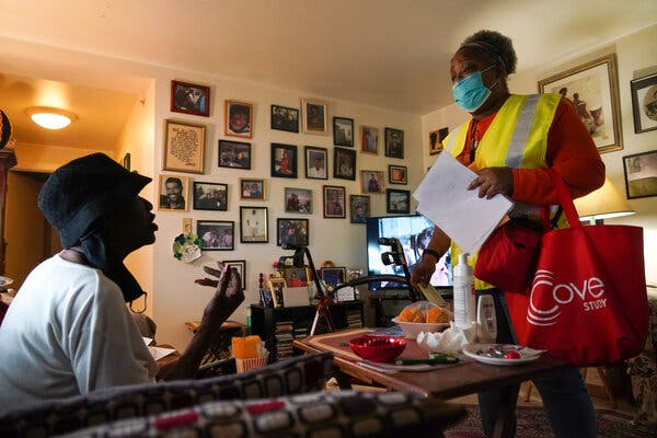 Carla Arnold, right, discussing volunteering for a coronavirus vaccine trial with Cecilia Goshay in Ms. Goshay's home.