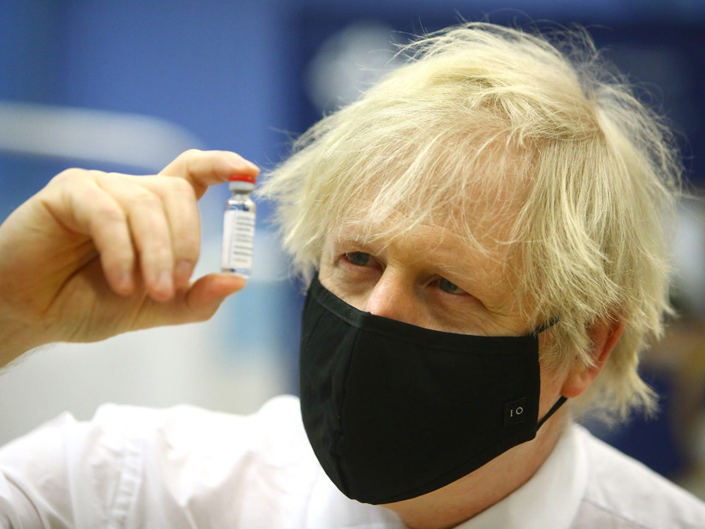 Britain's Prime Minister Boris Johnson poses with a vial of the Oxford/AstraZeneca vaccine as he visits a vaccination centre at Cwmbran Stadium in Cwmbran, south Wales on Feb. 17, 2021.