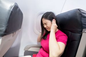 A woman grabs her ears while flying on an airplane