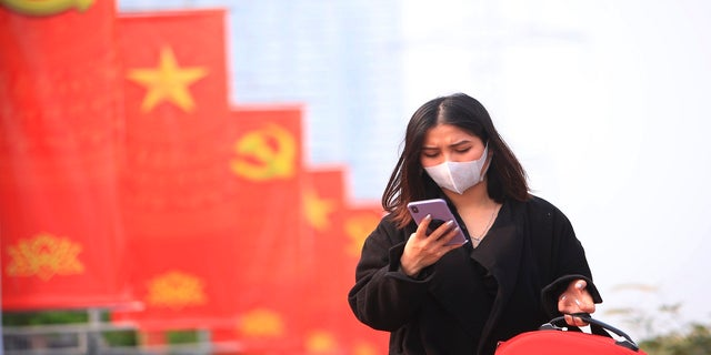 A woman wearing face mask looks at her phone in Hanoi, Vietnam. (AP Photo/Hau Dinh, File)