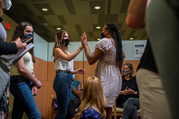 Many teenagers see the Covid shot as unlocking freedoms denied to them during the pandemic. In New Orleans, Ava Kreutziger, 14, left, high-fives Croix Hill, 15, after Croix received her first dose.