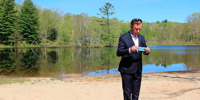 FILE - This photo from May 21, 2020, shows Connecticut Gov. Ned Lamont as he prepares to put on a face mask before his daily COVID-19 briefing, Gay City State Park in Hebron, Conn. Lamont's office say they will no longer provide daily updates on the number of people who have died in the state from COVID-19-related causes. (AP Photo/Pat Eaton-Robb, File)
